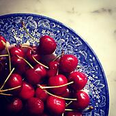 Red cherries in blue bowl. - Stock Image - S054W1