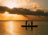 Family in outrigger canoe spearfishing on Aitutaki Island lagoon in the Cook Islands at sunset - Stock Image - C86PR5