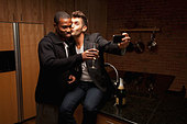 Gay couple drinking wine in kitchen and taking self-portraits - Stock Image - CTH11F