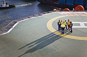 Workers talking on helipad of oil rig - Stock Image - C6YNDE