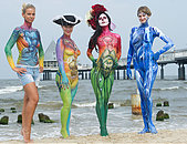 Heringsdorf, Germany. 15th Aug, 2015. Models Jenny, Katrin, Tina and Natalia (L-R) present creations by body painting artists taking part in a body painting festival at a beach of the sea beach resort Heringsdorf on Usedom island, Germany, 15 August 2015. Models need to be patient as the painting procedure will usually require them to sit still for several hours. Photo: STEFAN SAUER/dpa © dpa picture alliance/Alamy Live News - Stock Image - F0G9E2