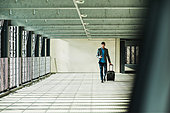 Young businessman walking in car park looking on cell phone - Stock Image - EJXJMM