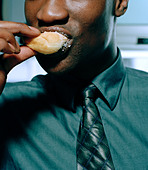office worker eating donut - Stock Image - A764EB