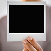 Hand holding blank Polaroid picture film - Stock Image - BPF4E8