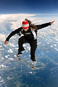 Skateboarder high above the clouds performing a trick - Stock Image - BYC1PM