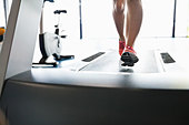 Low section of woman running on treadmill in fitness center - Stock Image - DA72XC