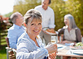 Portrait of smiling senior woman enjoying lunch with friends at sunny table - Stock Image - CC9JPF
