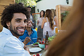 Portrait smiling man eating lunch at patio table - Stock Image - ERBW3W