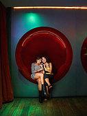 Hispanic women talking on cell phone in nightclub - Stock Image - AY6PGK