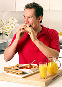 MAN EATING SANDWICH LUNCH - Stock Image - A5GXJY