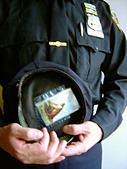 Artistic Portrait of a New York City Police Officer Holding His Hat Which Has a Prayer Card With An Image of Jesus Christ On It - Stock Image - AT6AYR