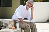 Businessman on lunch break talking on phone - Stock Image - EA6JN2