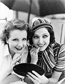 Two women putting on makeup - Stock Image - B32P91