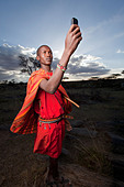 Maasai holding up mobile phone to get better reception, Mara Region, Kenya. - Stock Image - DERW3X