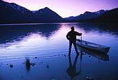 Sunset Silhouette of Canoe Man Trail Lake KP Summer AK Kenai Mts w w o man - Stock Image - AMYD5B