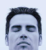 Close up portrait of young man  eyes closed  blue toned - Stock Image - A049B0