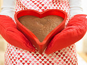 Close up of woman holding heart-shaped cake - Stock Image - BDMGA8