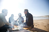 Group of friends sitting around a barbeque on the beach - Stock Image - BKXH2H