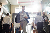 Men holding documents and running in office corridor - Stock Image - ECX7N5