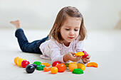 4-year-old girl playing with plastic fruits and vegetables. - Stock Image - E5R53K