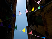 A view looking up through some colourful bunting  and roofs to a blue sky in downtown agde, france - Stock Image - ARFXTB