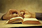 Two people holding hands over an open book - Stock Image - C9DBNY