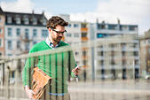 Man in green sweater carrying briefcase, reading text message - Stock Image - EMD2XA