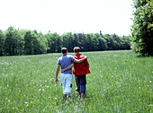 a gay couple walking in the grass view from behind - Stock Image - AAY58A