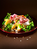 Peach and melon salad, with parma ham (prosciutto), almonds and lamb's lettuce. - Stock Image - BFBHC2