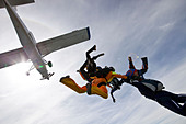Formation skydivers holding hands and rushing in freefall points together. Fun in a team with respect to the sport and danger. - Stock Image - BJ0TC2