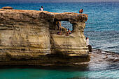 Tourists on the rock cave formations at Cape Greco, Cyprus. - Stock Image - ECYKMC