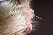 A woman tossing her hair with her mouth open - Stock Image - B0X3NC