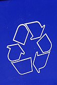 Closeup Detail of the Recycle Symbol on a Blue Recycling Bin Copy Space - Stock Image - B4BDG9