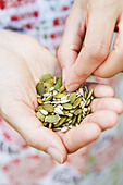 Close Up Of Woman Eating A Handful Of Healthy Seeds - Stock Image - CX6F24