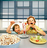 Two boys eating junk food - Stock Image - BBYND4