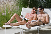 Gay couple relaxing by swimming pool - Stock Image - AHNAFN