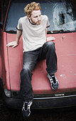 a portrait of a young guy sitting on the hood of an old car - Stock Image - AP7G16