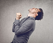 Young man in grey shirt rejoicing for his success - Stock Image - DGXJWB