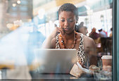African American woman using laptop in cafe - Stock Image - DYNDFF
