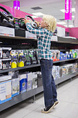 Boy reaching up for video game steering wheel in electronics store - Stock Image - DE152G