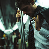 Man holding onto pole in subway car - Stock Image - BCKW8R