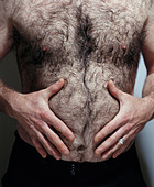 hairy man rubbing stomach - Stock Image - B1TYJW