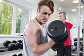 Man lifting weights in gym - Stock Image - CT1DGX