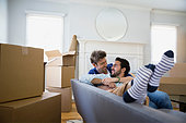 Affectionate homosexual couple relaxing sofa among moving boxes - Stock Image - ERBP7R
