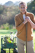 Portrait of smiling senior man with gardening tools - Stock Image - C93398