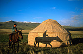 Horse and rider in front of a yurt, Moldo-Too Mountain Range, Song-Kul, Kyrgyzstan, Central Asia - Stock Image - C15FR2