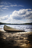 USA canoe boat beached on the shore of lake or river - Stock Image - DRF9T1