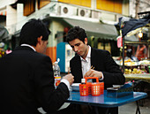 Businessmen eating lunch together outdoors - Stock Image - C6EP50