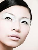 A young woman wearing a false eyelash - Stock Image - B56JYW
