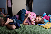 Two girls wrestling on the bed - Stock Image - CEW62A